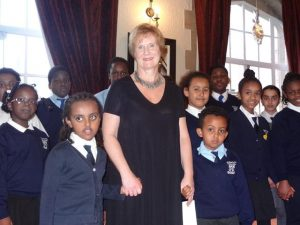 Headteacher Liz Holliday with two 'Bug Club' members and the choir in the background